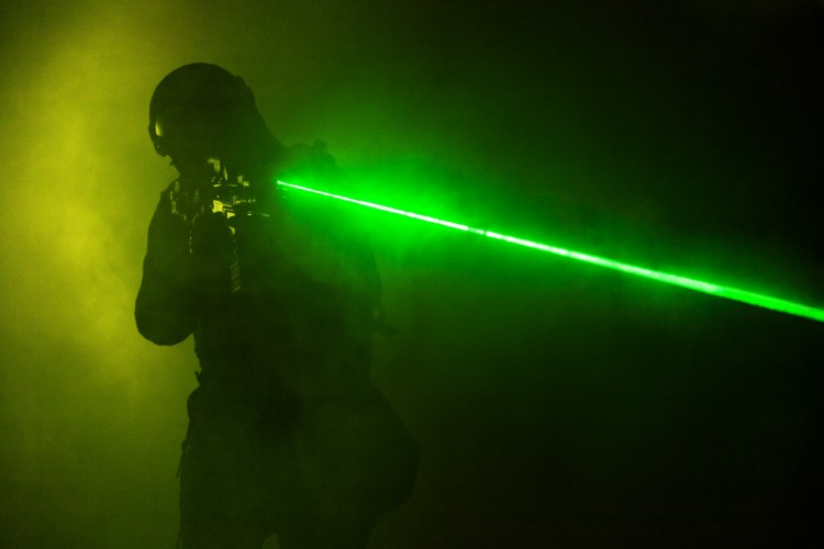 Police officer SWAT in black uniform in the smoke with laser sights